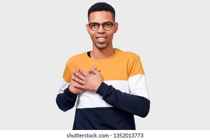 Candid portrait of kind dark-skinned man keeps both palms on chest, expresses kindness. Afro male looks directly to camera, in casual outfit, isolated over white background. People and body language
