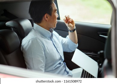 Candid portrait of a professional and handsome Chinese Asian businessman commuting to work in the backseat of a car that he booked via a ride hailing app. He is taking a break and looks out the window