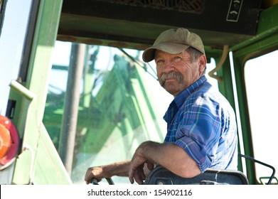 A candid portrait of a senior male farmer sitting in a tractor.