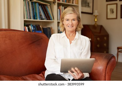 Candid portrait of a senior woman sitting on her favourite leather couch in her living room, using a digtital tablet