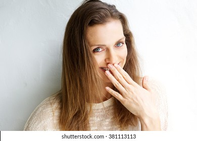 Candid portrait of a smiling woman with hand covering mouth