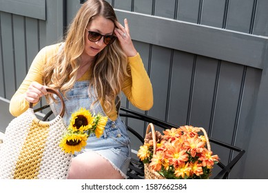 candid portrait of stylish young woman buying flowers at farmers market