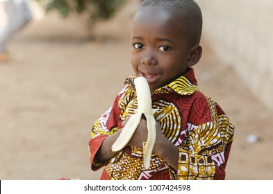 Candid Shot of African Black Boy Eating Banana Outdoor