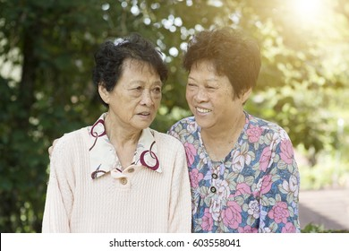 Candid shot of Asian elderly women talking at outdoor park in the morning.
