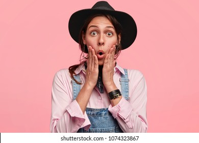 Candid shot of beautiful astonished female farmer, wears uniform, works hard on farm, shocked to see uncultivated crop, isolated over pink background. Surprised young woman gardener in black hat