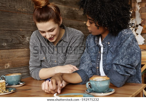 Candid shot of beautiful interracial homosexual female couple spending nice time together, sitting at cafe table with mugs and dessert, sharing sweet moment of their love. People and relationships