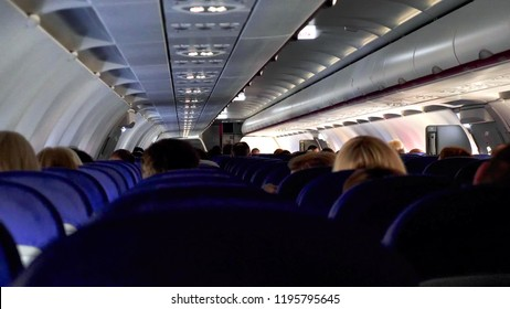Candid shot between seats of passengers sitting inside airplane while traveling