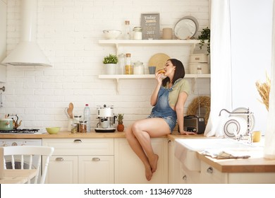 Candid shot of casually dressed young plus size female sitting barefooted on kitchen table and enjoying chocolate doughnut, failed at sugar free low calories diet. Food, nutrition and health