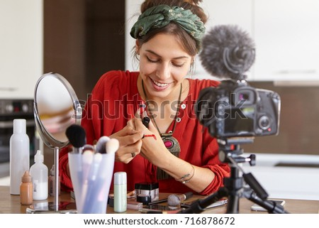 Candid shot of charming young lady video blogger talking on mass market cosmetics swatching lip gloss at home, sharing tips and recommendations on which beauty products choose via social networks