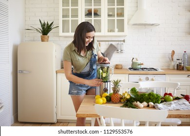 Candid shot of cheerful young plus size female wearing stylish denim jumpsuit making detox shake in blender. Happy smiling chubby girl blending broccoli, avocado and spinach for healthy smoothie