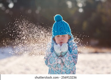 Candid shot of a cute little girl blowing snow flakes from her hands outdoors on a sunny winter's day
