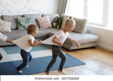 Candid shot of emotional Caucasian children siblings doing conga or dancing barefooted at home, playing indoor games on rainy cold weather, having happy excited facial expressions. Joy and fun