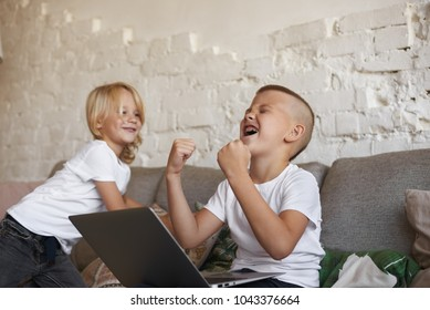 Candid shot of emotional ecstatic teenage boy with braces sitting on couch with his little brother, using laptop computer, shouting and pumping fists, rejoicing at his winning in video game