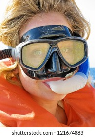 Candid shot,  extreme close up, head shot,  as a  young lady looks at the camera donning her old well used mask, snorkel, and life jacket, ready to head in to snorkel now.