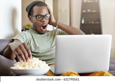 Candid shot of funny young dark-skinned man in eyewear and hat watching footbal match online, using laptop computer and eating popcorn, sitting on comfortable grey sofa at home, touching face in shock