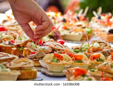 Candid shot of human taking canape party catering. Outdoor shot.