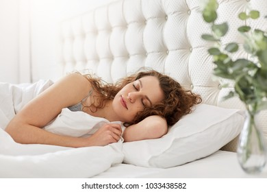 Candid shot of pleased young woman enjoys good sleep in bedroom, lies in comfortable bed, has appealing appearance, keeps eyes closed, lies under white bedclothes. Beautiful female has rest.