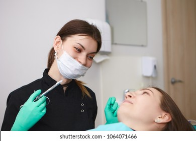 Candid shot of positive professional female dentist wearing mask and gloves holding syringe, going to anesthetize tooth nerve of smiling woman patient before dental treatment. Anesthesia and numbing