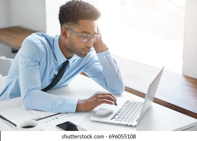Candid shot of stylish young Afro American unshaven manager wearing formal shirt and glasses having bored look, wasting his time using laptop pc, browsing internet, doing nothing instead of working