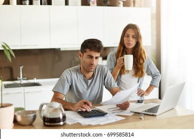 Candid shot of young American couple managing family budget, reviewing bank accounts using laptop and calculator in kitchen. Man and woman doing paperwork together, paying taxes online on notebook pc