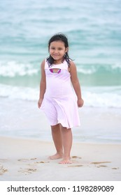 Candid Shyness of a Cute Little Girl Toothless Wearing Pink Dress Pursuit of Portraits in a Paradisiac Scenery in The Famous Rio de Janeiro 's Atlantic Shore During Summer Vacation