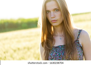 Candid skipping carefree adorable woman in field of flowers at summer sunset