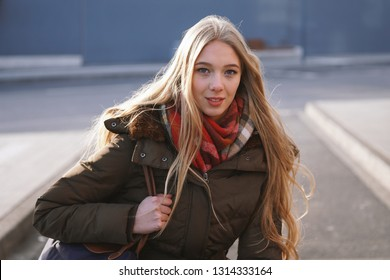 candid street style portrait of teenage girl waiting at bus stop on a sunny day in winter
