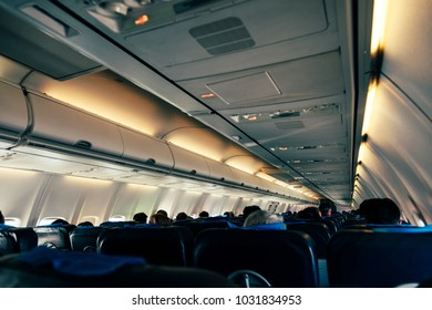 Candid view of an airplane's fuselage with passengers in their seats.