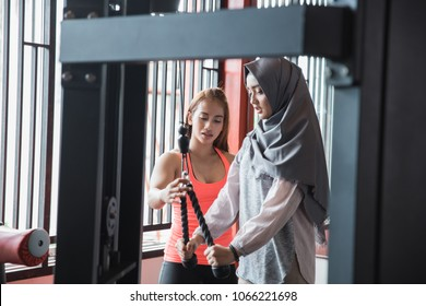 Candid view of young asian muslim woman hijab exercising triceps pushdown at the rope cable machine in a fitness club with trainer