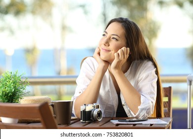 Candid woman dreaming during a beach travel sitting in an apartment terrace