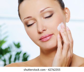Candid woman face with closed eyes applying  moisturizer cream on her cheek
