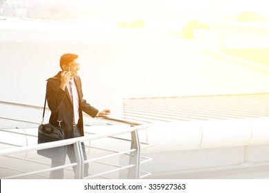 Candid young Asian Indian businessman on the phone at outdoor office building. India male business man, sunset light at background.