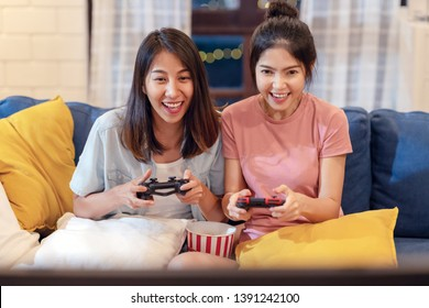 Candid of young attractive asian homosexual couple of lesbian woman sitting on couch in living room at home enjoy and excited holding console playing game together. LGBT family pride in asian concept.