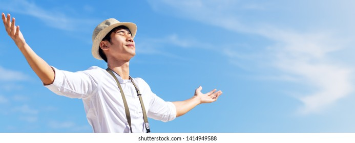 Candid of young attractive asian man close eyes, deep breath and wide open arms in blue sky view background feeling wind and sunshine. Happy asian hipster male in youth freedom culture travel concept.
