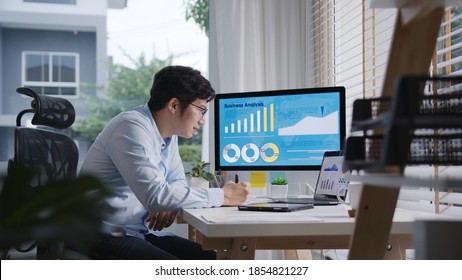 Candid of young attractive asian thai man busy work multiple screen computer or smart tablet on table desk at home in freelance data analyst, data science scientist for business.