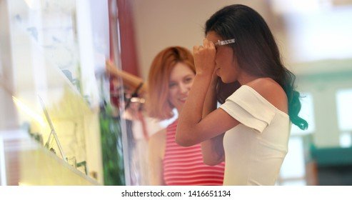 Candid young multiracial women shopping for sunglasses. Pretty girls trying on sunwear at store