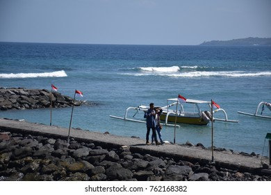 CANDIDASA, BALI - AUGUST 23 - Balinese couple walk on a pathway near the sea on august 23, 2017 in Candidasa