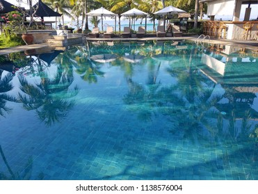 CANDIDASA, BALI, INDONESIA - MAY 17, 2017: Pool and bar amenities surrounded by palm trees, in a Candidasa beach resort in Bali, Indonesia, for travel backgrounds.