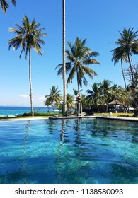 CANDIDASA, BALI, INDONESIA - MAY 17, 2017: Infinity pool and palm trees, by the Indian Ocean in a Bali, Indonesia resort with copy space for travel backgrounds.