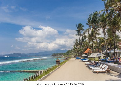 CANDIDASA, INDONESIA - OCTOBER 14, 2018: Sunbeds at a hotel on the Candidasa coast of Bali, Indonesia