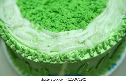 "Candied coconut slivers top a cake made with pandan icing.  Coconut, locally known as ""buko"", is usually paired with pandan in Filipino desserts, and when so combined, is referred to as ""buko pandan""."