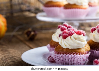Candied cranberries and cream cheese  homemade cupcakes on wooden board. Homemade autumn holiday dessert on  rustic table