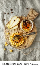 candied fruit jelly. pear marmalade with coffee beans. Jar of pear jam on wooden cutting board on linen background