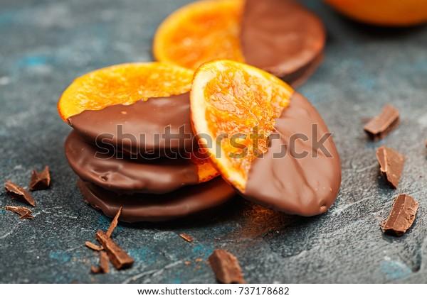Candied orange slices in chocolate on dark blue  background.