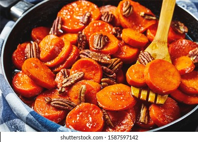 Candied sweet potatoes with brown sugar, maple syrup, orange juice and pecan nuts in a skillet with wooden spatula, view from above, close-up, macro