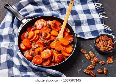 Candied sweet potatoes with brown sugar, maple syrup, orange juice and pecan nuts in a skillet on a concrete table with kitchen towel, view from above, close-up