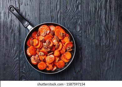 Candied sweet potatoes with brown sugar, maple syrup, orange juice and pecan nuts in a skillet on a black wooden table, horizontal view from above, flatlay, free space