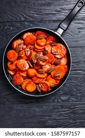 Candied sweet potatoes with brown sugar, maple syrup, orange juice and pecan nuts in a skillet on a black wooden table, vertical view from above, free space