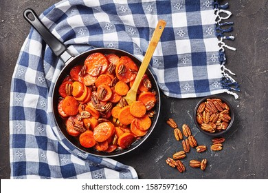Candied sweet potatoes with brown sugar, maple syrup, orange juice and pecan nuts in a skillet on a concrete table with kitchen towel, view from above