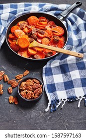 Candied sweet potatoes with brown sugar, maple syrup, orange juice and pecan nuts in a skillet on a concrete table with kitchen towel, vertical view from above